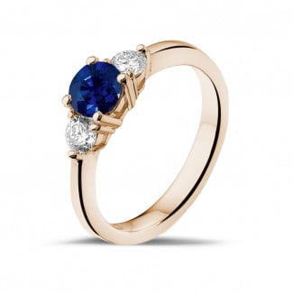 Red Gold Diamond Engagement Rings - Trilogy ring in red gold with a central sapphire and 2 round diamonds