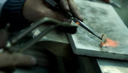 Edelsmid maakt een gouden ring en maakt zo ook de gouden ketting en andere juwelen van BAUNAT